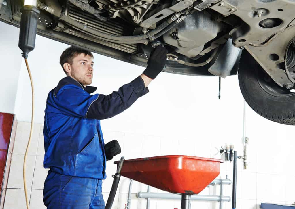 Car servicing, replacing of motor oil and filter at auto repair shop